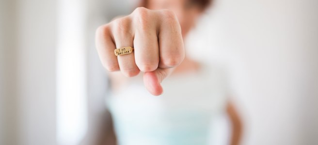 "A woman wearing a ring that says, ""I am a badass"""