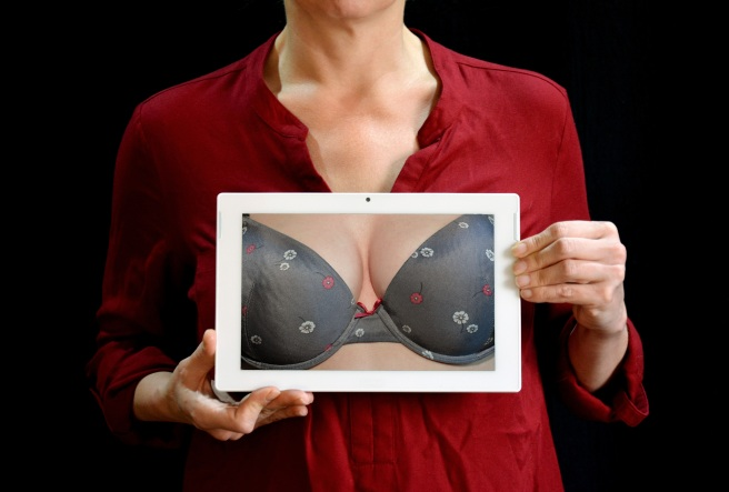 Woman holding a picture of a bra