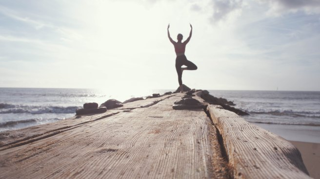 Woman doing yoga at the end of a pier