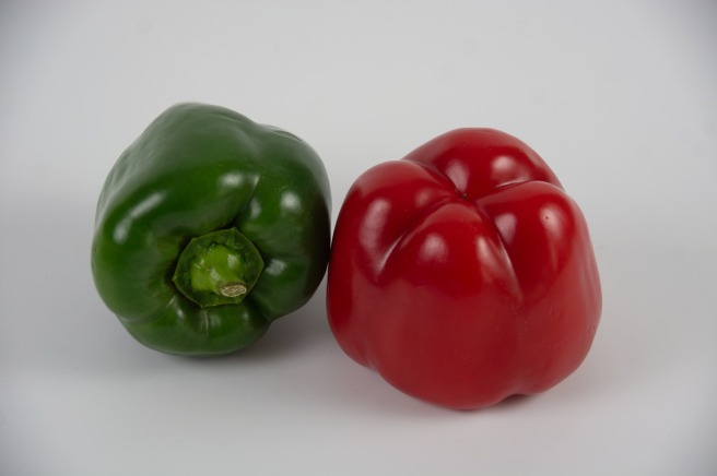 A red and a green bell pepper
