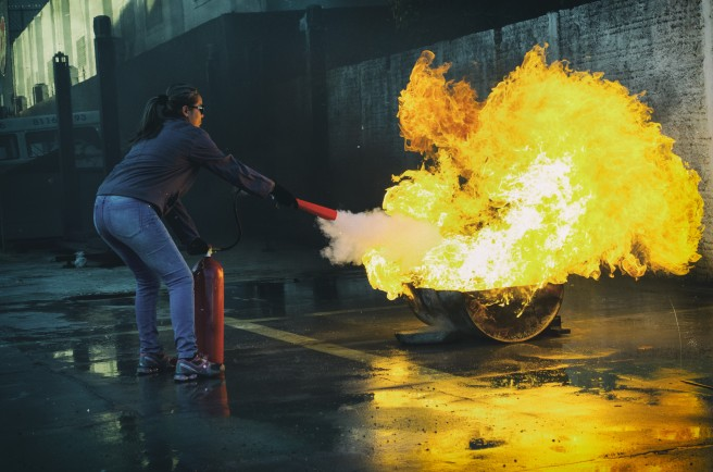 Woman putting out a fire with an extinguisher