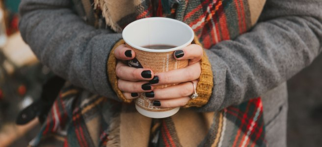 Girl with a scarf holding a cup of coffee.