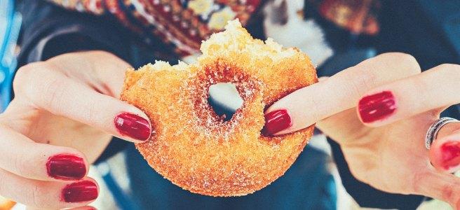 Girl holding a half-eaten donut