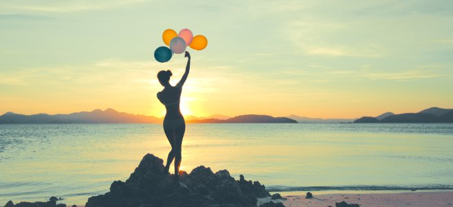 Woman on the beach letting balloons go