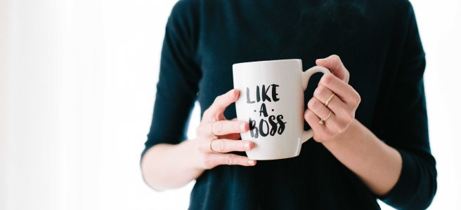 Woman holding a mug that says like a boss