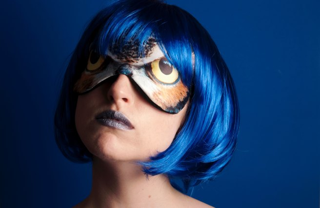 Woman in a blue wig and owl mask
