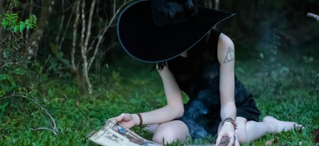Woman in a witch hat reading a magic book